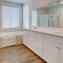 The owner's bath, featuring dual sinks, soaking tub, and step-in shower.
