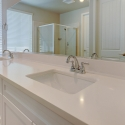 Closeup of the dual sinks and white quartz countertop in the owner's bath.