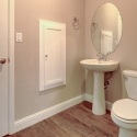 The downstairs powder bathroom, featuring built-in medicine cabinet and linen closet.