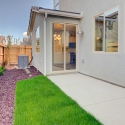 The landscaped backyard, with uncovered patio and sliding glass door leading to the dining nook.