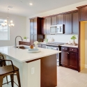 The kitchen, featuring large kitchen island and dark java cabinets.