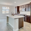 The kitchen, featuring a large kitchen island and dark java cabinets.