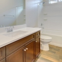 The second bathroom, featuring white quartz countertops and dark java cabinets.