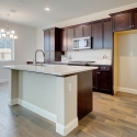 The kitchen, featuring large kitchen island, white quartz countertops, and dark java cabinets.