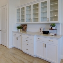 The storage hutch located across from the ktichen, with glass front upper cabinets.