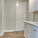 The laundry room, with utility sink, and upper and lower cabinets.