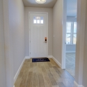 The white front entry door, as seen from the hallway. The door to the downstairs bedroom is to the right.