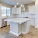 The kitchen, featuring white cabinets and a white subway tile backsplash.