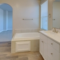 Dual sinks and tiled-in bathtub in the owner's bath.