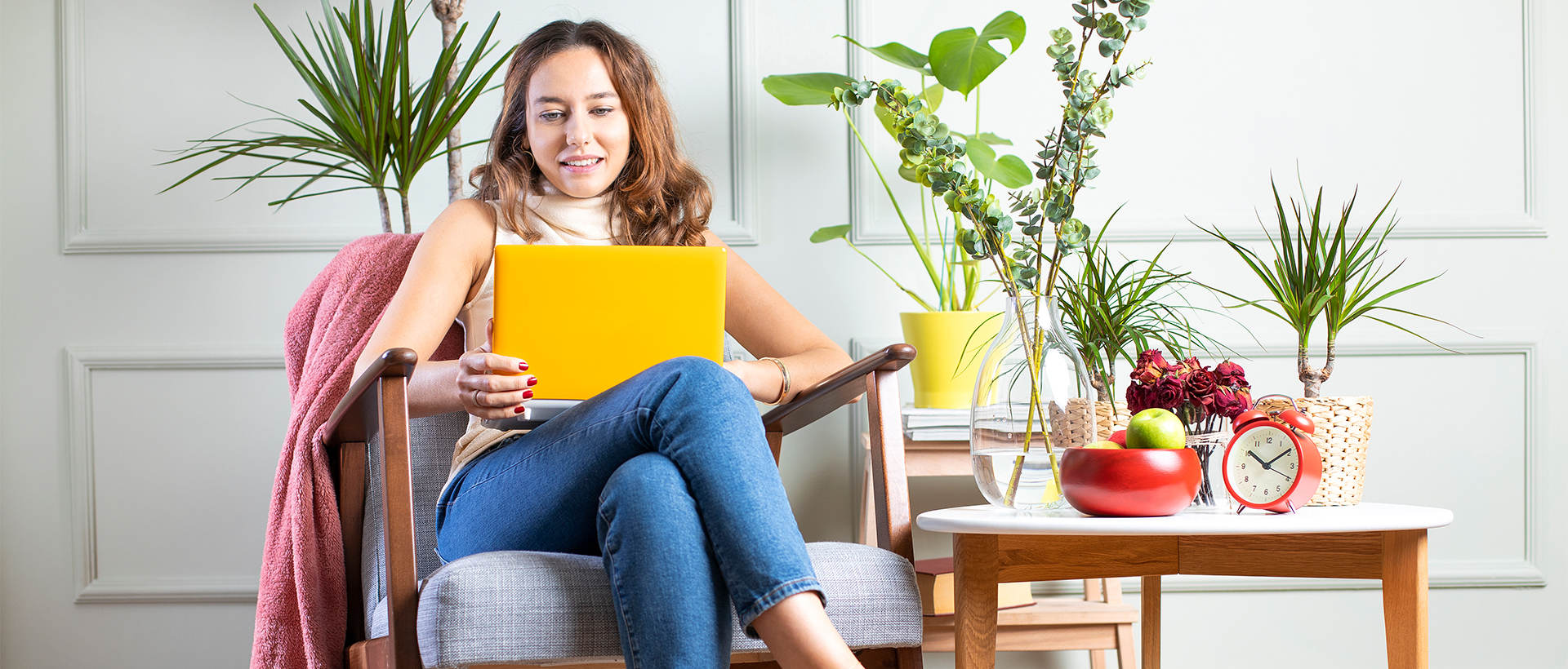 A woman surrounded by houseplants taking an online course on her laptop.