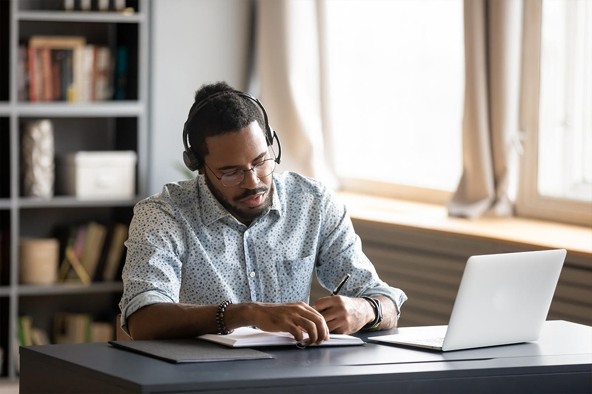 A man listening to an audiobook while working from home.