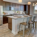 The kitchen, featuring large kitchen island and dark hava cabinets.