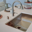 The stainless steel kitchen sink.