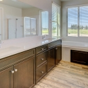 The spacious owner's bath, featuring dark java cabinets, a tiled-in soaking tub, and large step-in shower.