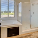 The tiled-in soaking tub and tiled shower in the owner's bath.
