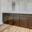 The dark java cabinets and dual sinks in the owner's bath.