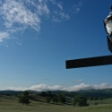 Artistic shot of a corner sign post in Ventana Hills, set against a bright blue sky. The rolling hills can be seen in the background.