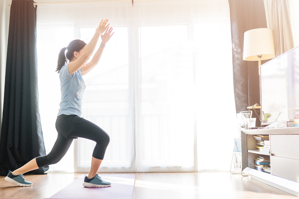 A woman following along with an on-demand online workout video in her living room.
