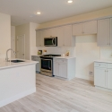 The spacious kitchen, which features grey shaker cabinets, white quartz counters, and a large kitchen island.