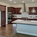 The kitchen, featuring dark coffee-stained cabinets and white quartz cabinets.