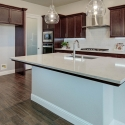 The large kitchen island with glass pendant lights hanging above.