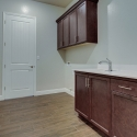 The laundry room, with upper and lower cabinets and included cast iron utility sink.