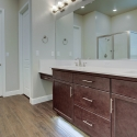 The owner's bath, with under cabinet lighting and dark coffee-stained cabinets.