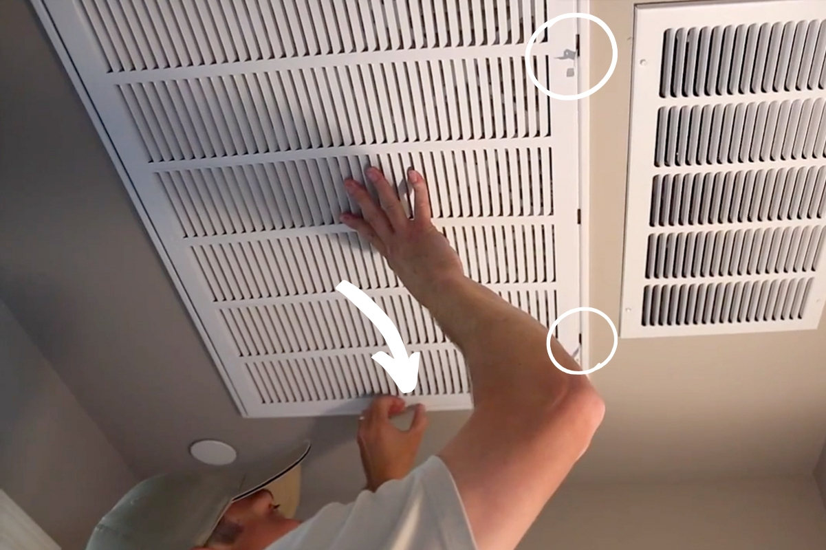 Circle outlines indicate the location of the tabs on the AC filter grate. A worker is using one hand to support the grate while opening up the tabs.