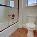 The toilet and tile wall tub in the second bath's water closet.