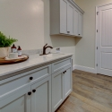The laundry room, with upper and lower cabinets, and a cast iron utility sink.