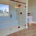 The tile-wall shower in the owner's bath, with dual showerheads and frameless glass door