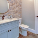 The powder bath, featuring a brick accent wall that is found throughout the rest of the home.
