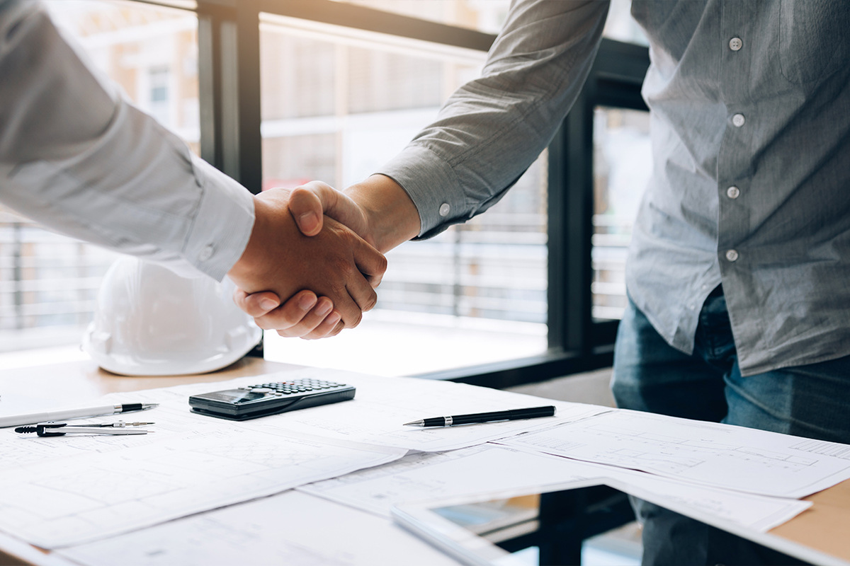 Two people shaking hands after signing a contract.