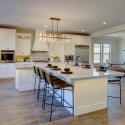 The expansive kitchen, featuring white cabinets and countertops, modern chandelier, and expansive T-shaped kitchen island.