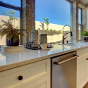 Large windows behind the sink and dual dishwashers in the kitchen provide a wide view of the backyard.