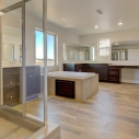 The spacious, spa-like owner's bath, which features a glass-walled step-in shower and a large tiled-in soaking tub at the center of the room.
