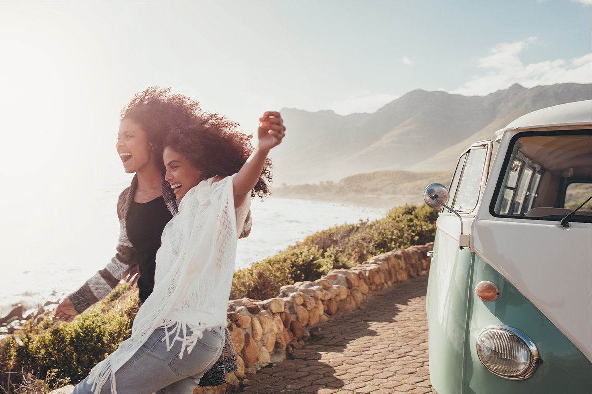 Two young women excitedly leave their car after arriving at the California coast.
