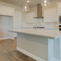 The kitchen, featuring white cabinets and quartz countertops.