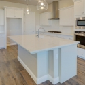 The large kitchen island with white quartz countertop.