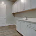 The laundry room, with upper and lower cabinetry and a utility sink.