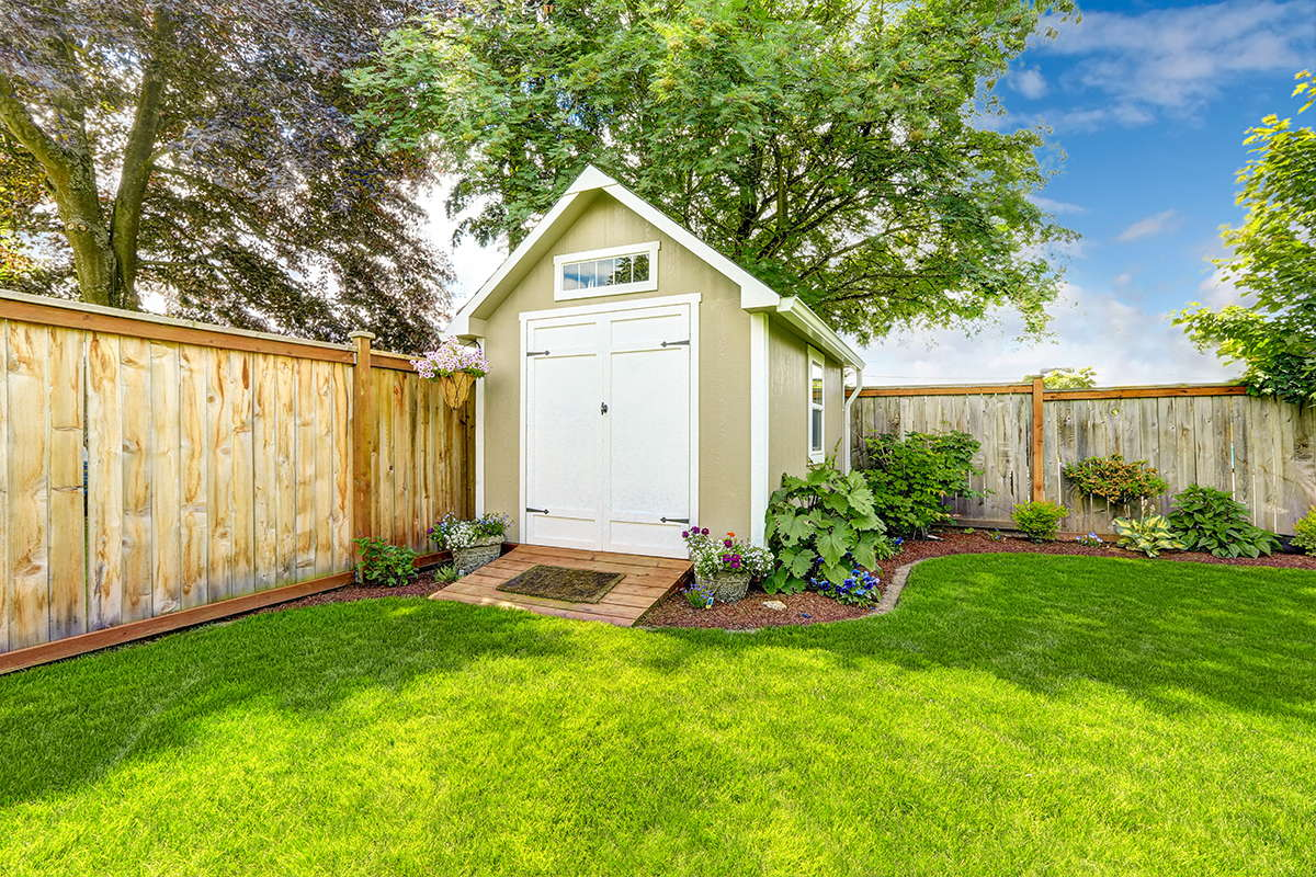 A cute shed in the backyard of a home.
