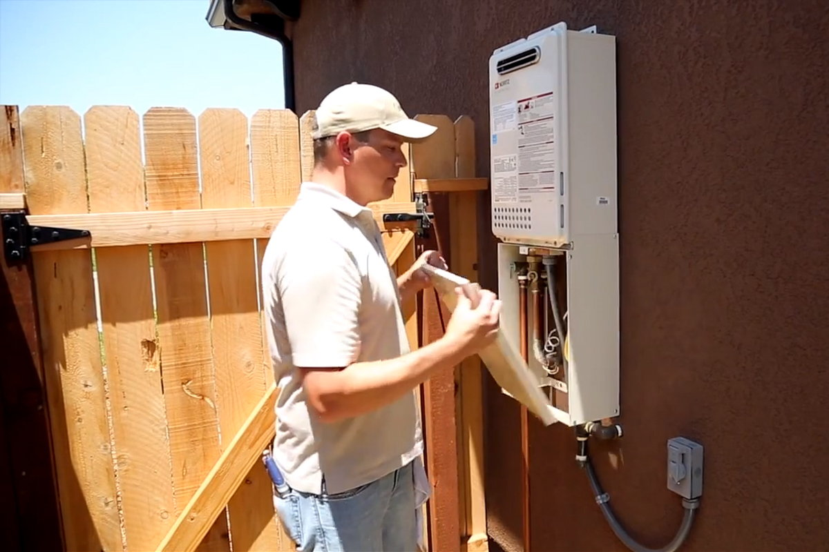 Removing the access panel on the tankless water heater.