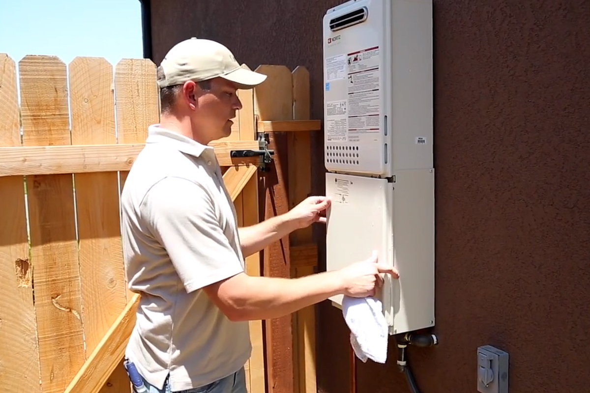 Putting the panel back onto the tankless filter.