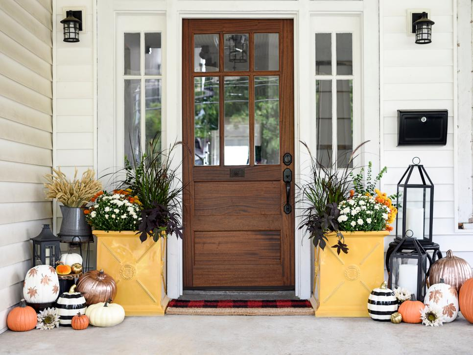 A patio decorated with fall flowers and foliage and pumpkins painted in shades of black, white, orange, and gold.