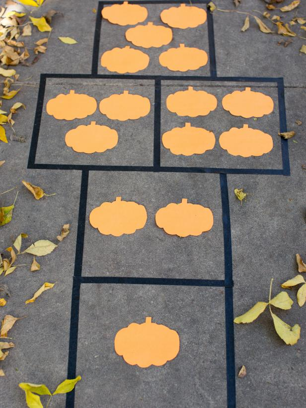 A halloween themed hopscotch board with cutout pumpkins in place of the numbers.