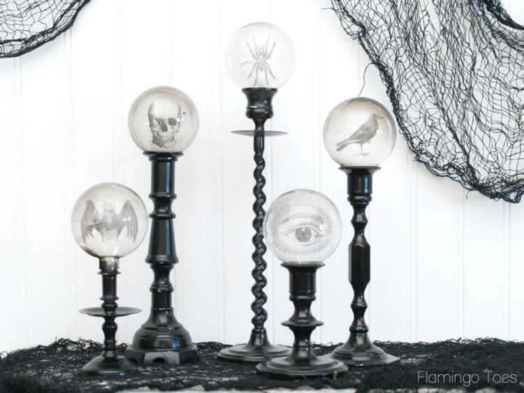 Black and white images appear to float inside of crystal balls atop black pedestals in this creative DIY.