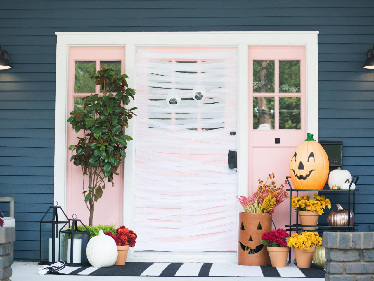 A pink front entry door decorated with crepe paper ribbons and large googly eyes, resembling a large mummy.