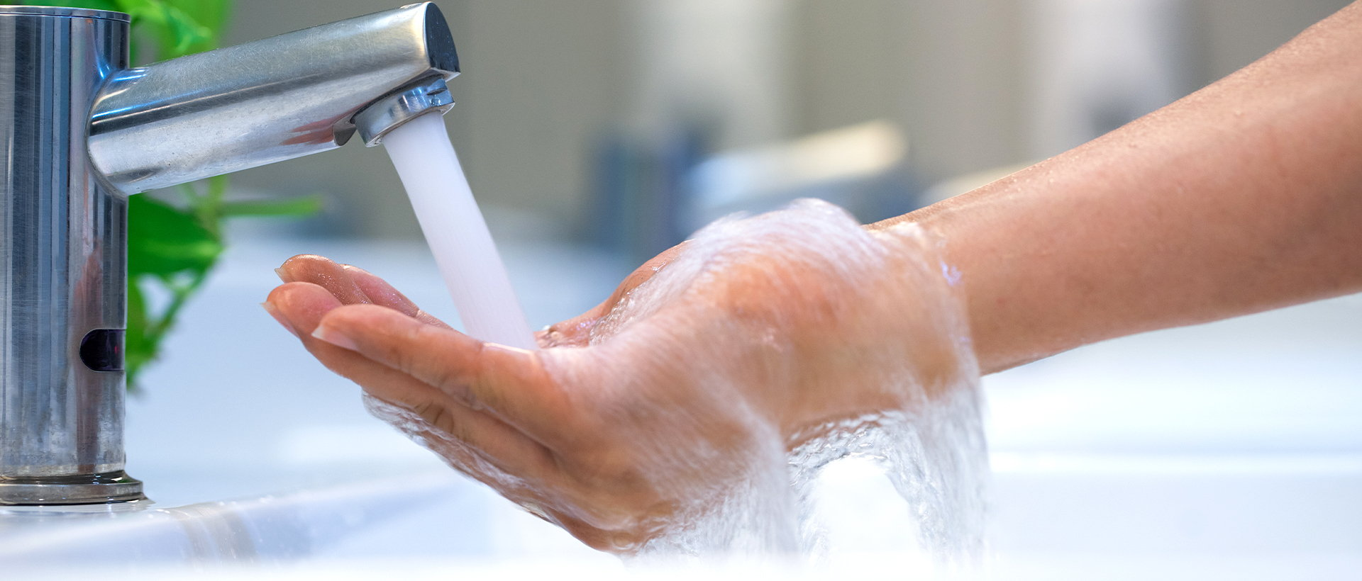 A hand under warm water running from a faucet.
