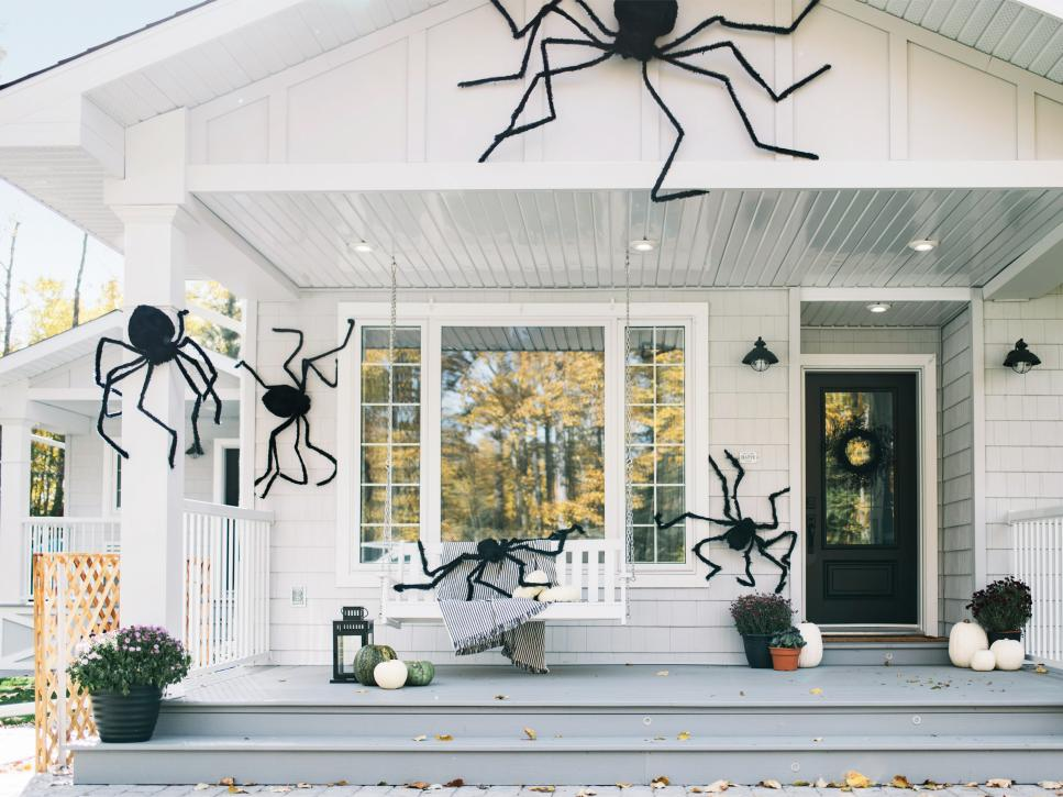A white farmhouse style home decorated with large spider decorations for Halloween.