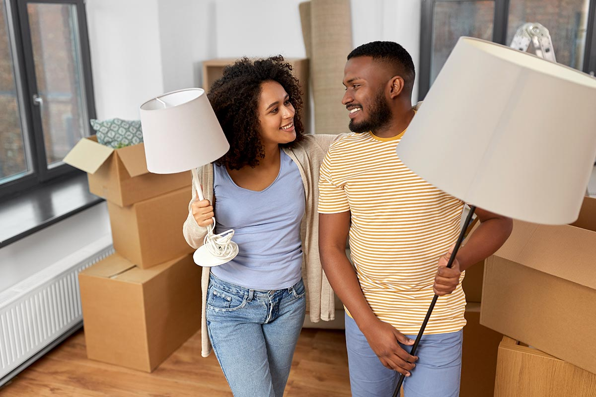 Couple moving holding lamps with boxes in the background